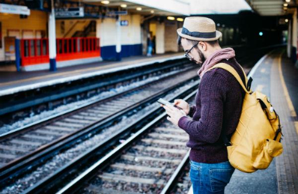 social-media-detox-man-staring-at-phone-by-train
