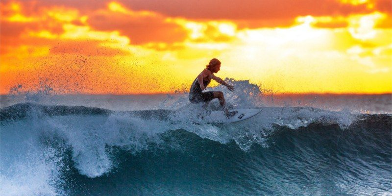 Surfer on wave at dawn