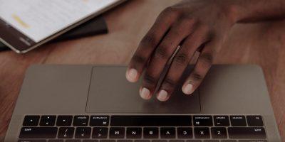 A hand reaching for a MacBook.