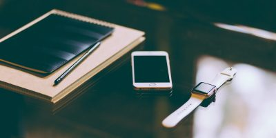 A desk showing an iPhone and Apple Watch.
