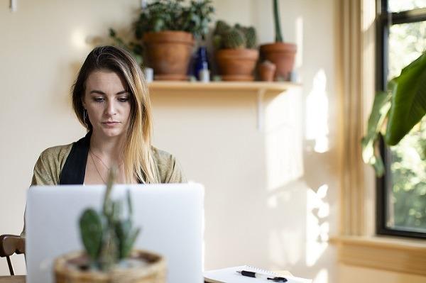 अपने लैपटॉप पर घर से काम करने वाली रिलैक्स्ड वुमन